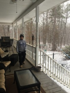 My daughter Faith enjoying the snow (from the porch that is!)